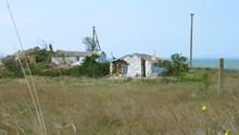 Old Destroyed White Houses On The Meadow Next To The Sea. Windy Weather.