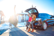 Winter Vacation. Family Time Together Outdoors Standing Sitting At Car Trunk With Skis Smiling Happy Side View