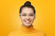 Close up shot of smiling attractive young woman isolated on yellow background