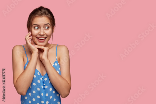 Fotografie, Obraz  Cute emotive glad woman with toothy smile, keeps hands near face, looks with hap