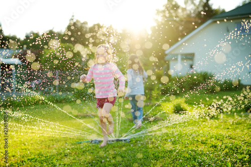 Slika na platnu Adorable little girls playing with a sprinkler in a backyard on sunny summer day