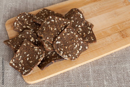 Fotografía  Croutons of rye bread with seeds on a cutting board. Copy space.