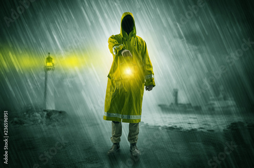 Foto  Man at the coast coming in raincoat with glowing lantern concept