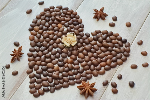 Foto  Heart of coffee beans with star of anise and satin in pastel shades of a rose on a light wooden background