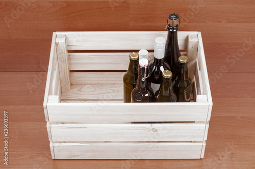 Tuinposter Bier / Cider Beer and wine bottles in wooden box on wooden background