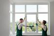 Leinwandbild Motiv Construction workers install a window