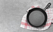 Cast Iron Pan On A Grunge Concrete Background With Copy Space. Empty Iron Pan, Top View Or High Angle Shot.