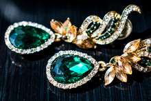 Metal Gold Earrings With Green, Emerald Stones, White And Yellow Rhinestones. On A Black Glossy Background. Glitters And Sparkles.
