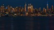 The New York City Skyline during the blue hour at twilight. Boats travel thru the Hudson River and passenger cars along midtown Manhattan.