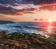 Amazing sunset on the ocean. View of dramatic cloudy sky and stony coast. Portugal. Concept of the harmony wiht wildlife, romance, emotional experience in your soul, joy in mundane life.