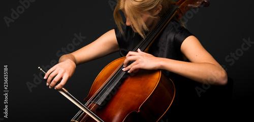 Slika na platnu Young girl playing the cello on isolated black background