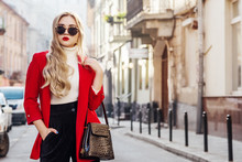 Outdoor Fashion Portrait Of Young Beautiful Fashionable Lady Wearing Stylish Glasses, White Turtleneck, Red Blazer, Holding Stylish Faux Reptile Skin Bag, Posing In Street Of European City. Copy Space