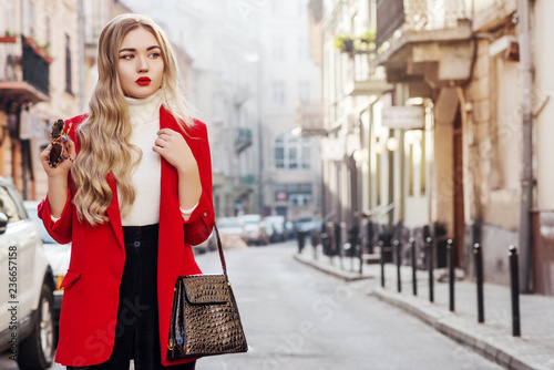 Outdoor fashion portrait of young beautiful fashionable woman wearing white turtleneck, red blazer, holding stylish faux reptile skin handbag, model posing in street of european city. Copy space