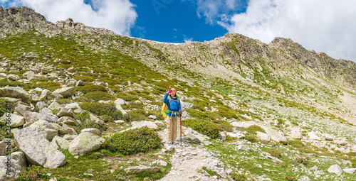 Fototapeta Happy woman hiker travels in Pyrenees Mountains in Andorra and Spain. Nordic walking, recreation and trekking along GR11 path trail obraz