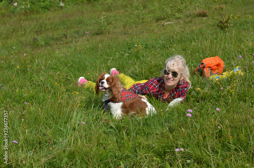 Fotografie, Obraz  Woman dressed in rustic royal stewart shirt, lying on green meadow resting with