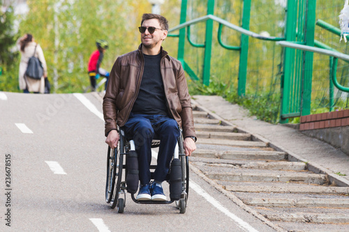 Valokuva  A young man in a wheelchair rides along the park road.