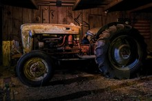 A Vintage Or Antique Tractor In An Old Dimly Lit Barn At Nighttime