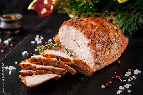 Roasted sliced Christmas ham of turkey on dark rustic background. Festival food.