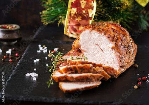 Roasted sliced Christmas ham of turkey on dark rustic background. Festival food.