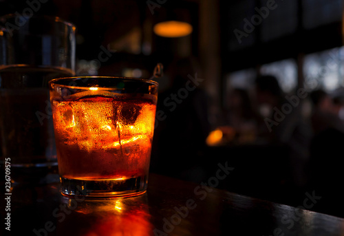 Cocktail close up in a dark bar setting. Drink is illuminated. Selective focus on the frosty drink and glass. Shadowy people in the background. Copy space.