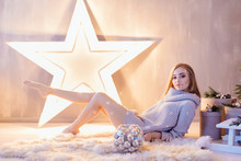 Beautiful Young Woman Sitting Next To The Big Star With Bowl Full Of Silver Balls In A Holiday Interior
