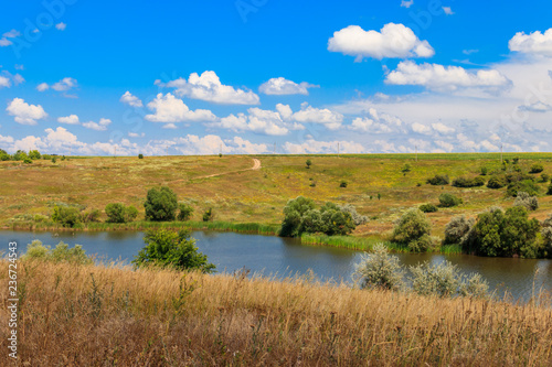 Poster Landscapes Summer landscape with beautiful lake, green meadows, hills, trees and blue sky