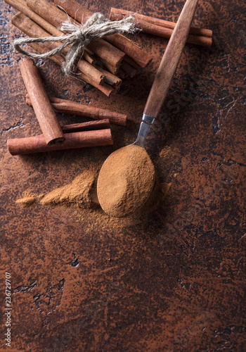 Cinnamon sticks and powder in spoon on a old copper table .