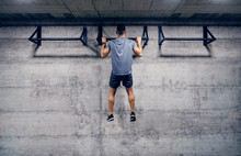 Caucasian Man Doing Pull-ups In The Gym. Strive For Progress And Perfection.