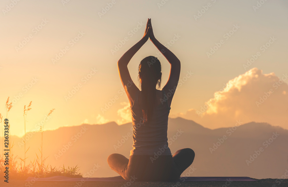 Fototapeta fitness girl practicing yoga on mountain