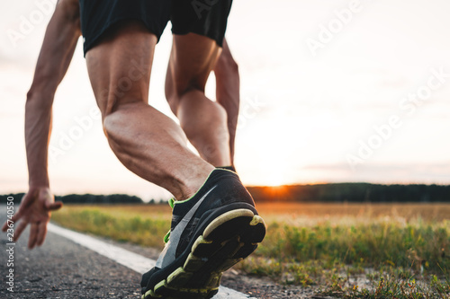 Fotografiet  Close up view on strong and muscular athlete runner feet in start pose on asphalt road outdoor