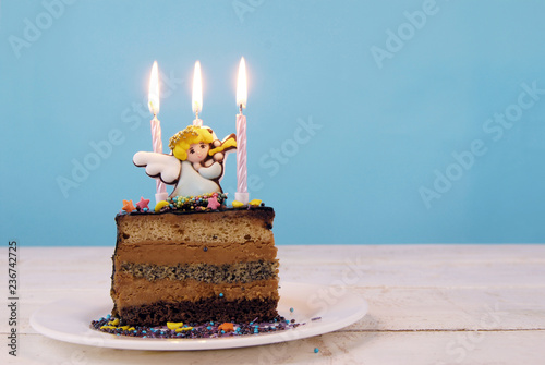 Childrens Birthday Cake Decorated With Marzipan Angel And Candles On A White Wooden Table