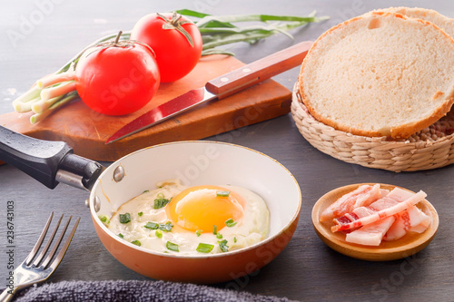 Fried egg in a pan, sliced bread, bacon, tomatoes and green onions cooked for breakfast on a wooden gray table.