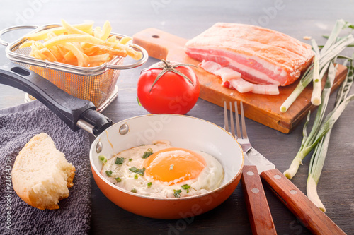Fried egg in a pan, sliced bread, bacon, french fries, tomatoes and green onions are cooked for breakfast on a wooden gray table.