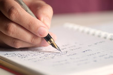 Close Up Of Female Hands With Pen Writing On Notebook