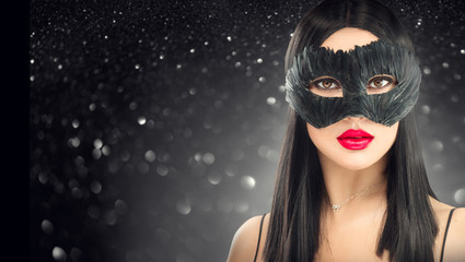 Beauty glamour brunette woman wearing carnival dark mask, party over holiday glowing black background