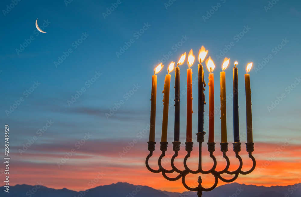 Fototapeta Burning candles in menorah are traditional symbols for Hebrew celebration of Hanukkah holiday. Background of sunrise and night mountain sky, selective focus on menorah