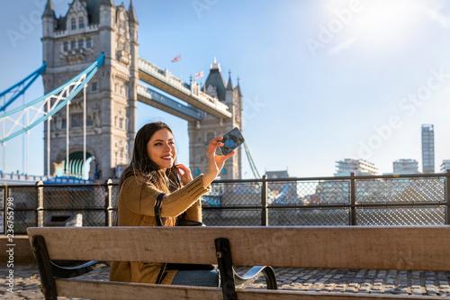 Fotografie, Tablou  Touristin auf einer Sightseeing Tour vor der Tower Bridge in London macht ein Se