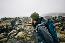 Young Man In Hiking Trekking Gear, Waterproof Jacket, Green Knit Beanie And Hike Backpack Walk Through Moss Covered Rough Iceland Terrain. Explore Travel Real Wilderness Lifestyle