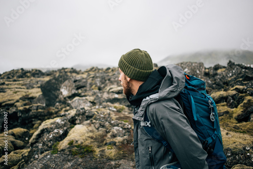 Obraz Young man in hiking trekking gear, waterproof jacket, green knit beanie and hike backpack walk through moss covered rough iceland terrain. Explore travel real wilderness lifestyle - fototapety do salonu