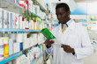 male pharmacist reading prescription medicines