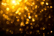 Christmas Golden Glowing Background. Holiday Abstract Defocused Backdrop. Tinsel Blurred Gold Bokeh On Black Background