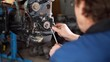repair of the engine of the car, the repairman is engaged in restoration of the engine of the motor