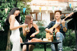 Women enjoying drinks party with guy playing guitar singing at home garden outdoors.
