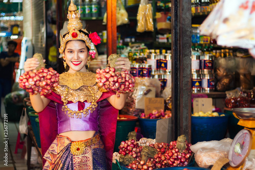 Poster Bangkok Woman wearing Thai style dress are Holding shallots in market.