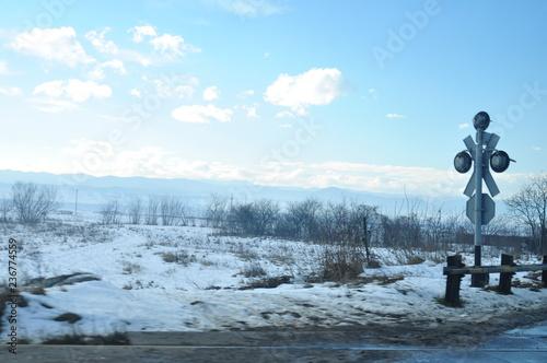Photo sur Toile Bleu clair route entre les champs enneigés avec passage de train