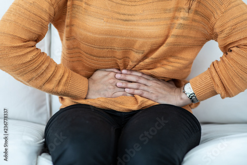woman have bladder pain sitting on sofa feeling so sick and painful,Healthcare c Canvas Print