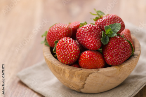 Ripe strawberries in wooden bowl on wood background with copy space