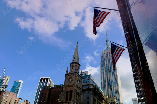 Fotografia  New York City - August 25, 2018: Empire State Building and US Flags