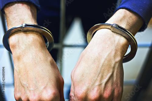 Fotografia  Male hands in metal handcuffs closeup