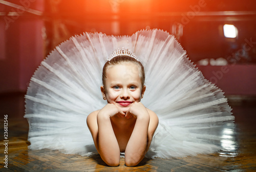 Fotografie, Obraz  A portrait of cute smiling ballerina in white tutu and crown laying on the wooden floor with face in hands